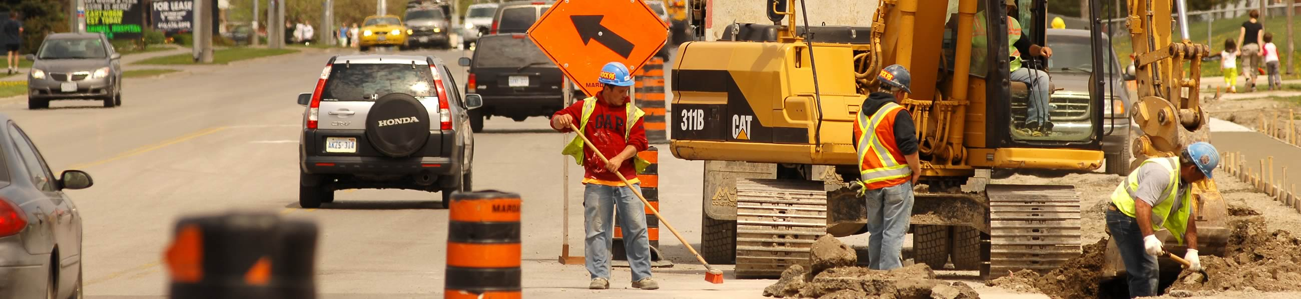 Construction workers digging a hole on a street in Barrie