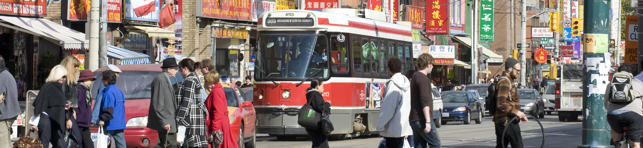 Traffic on busy street in Toronto, tram, cars and padestrian commuters
